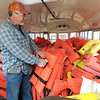 Big Elk Campground owner Pat Tinsley organizes some of the 700 life vests stored on a bus for the busy season in Pineville on Wednesday.<br /> Globe | Laurie Sisk