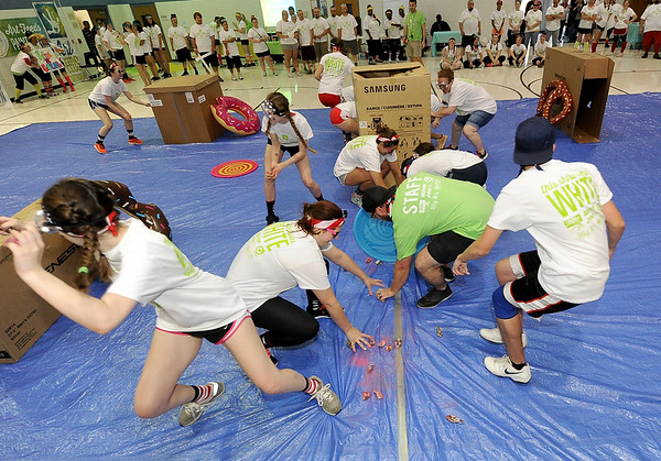 Competitors race to collect small packets of powdered tempra paint during Art Feeds Paint Wars on Saturday at McAuley High School.<br /> Globe | Laurie Sisk