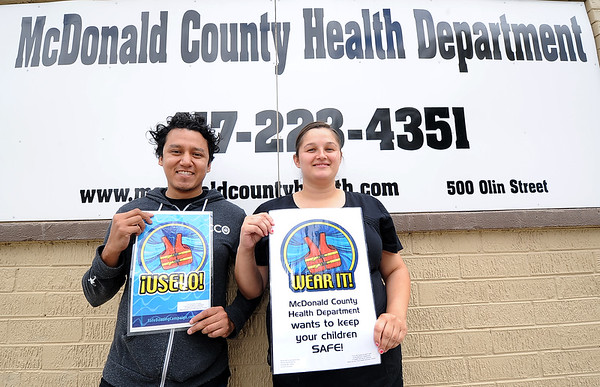 McDonald County nutritionist Roberto Correa, left and RN Kimberly McGhee hold bilingual signs reminding boaters and canoers in the county the importance of water safety.<br /> Globe | Laurie Sisk
