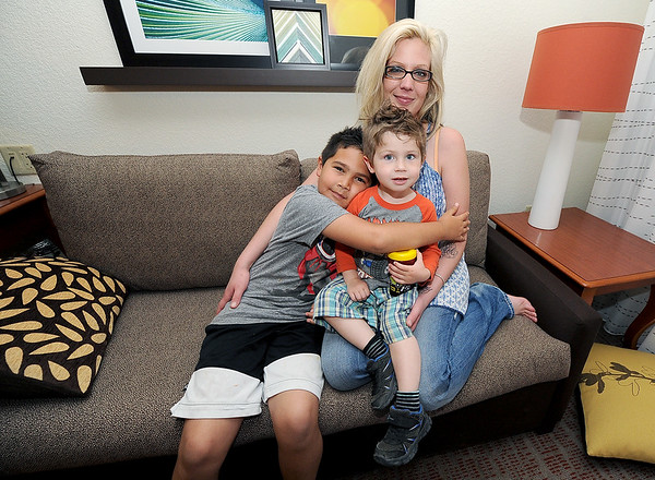 Bree O'Haro sits with her two sons, Dominick Sansalone, 9 and Draven Showalter, 2 inside their hotel room at the Residence Inn on Tuesday. The family was displaced from their Joplin home after a snafu on their sewer connection.<br /> Globe | Laurie Sisk