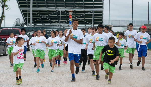Diego Vargas, 13, holds the torch as he runs with athletes from Neosho United Soccer Club and the Jopin Roadrunners on Friday at Missouri Southern during the Show-Me State Games Shelter Insurance Torch Run. The Show-Me State Games is an Olympic-style sports festival taking place in June and July in Columbia.