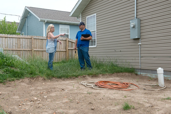 Globe/Roger Nomer<br /> Bree O'Haro shows Joshua Grosvenor, a mechanical engineer with DNR, the spot where sewage came out into her backyard during a tour of her house on Tuesday.