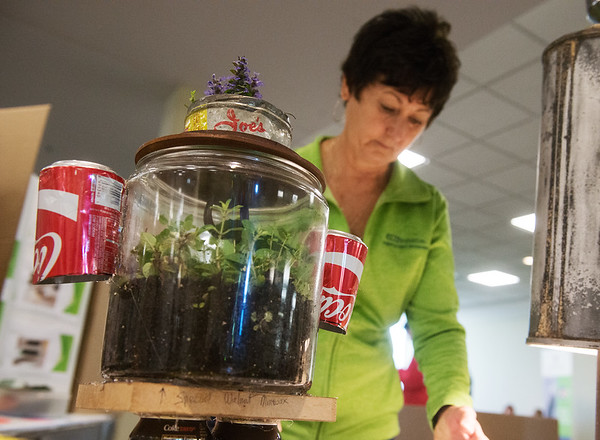 Globe/Roger Nomer<br /> Theresa Block, staff vice president of environmental affairs at Leggett and Platt, looks over recycled crafts, including a terrarium, on Tuesday at Missouri Southern.