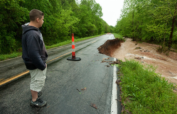 Zander Moreland, 13, on Saturday checks out a large chunk of Hwy NN near Anderson that collapsed  after heavy rains Friday night and Saturday caused massive flooding in the area.<br /> Globe | Laurie Sisk