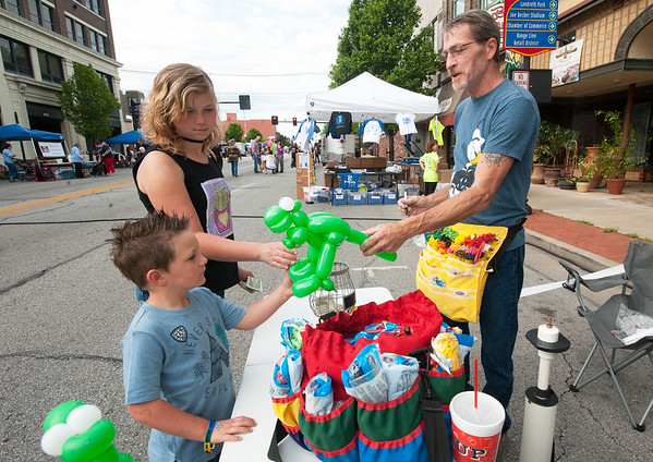 "From the left: Four-year-old Nathan DeArmond and big sister Joscelyn DeArmond, 10, get balloon animals from ""Twister"" Dex Miller during Third Thursday in downtown Joplin.<br /> Globe 