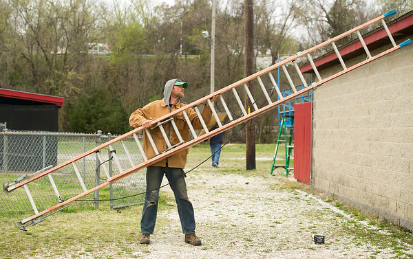 Matt Couch moves a ladder to work on the exterior of the press box at the Little League stadium at Landreth Park on Saturday.<br /> Globe | Laurie Sisk