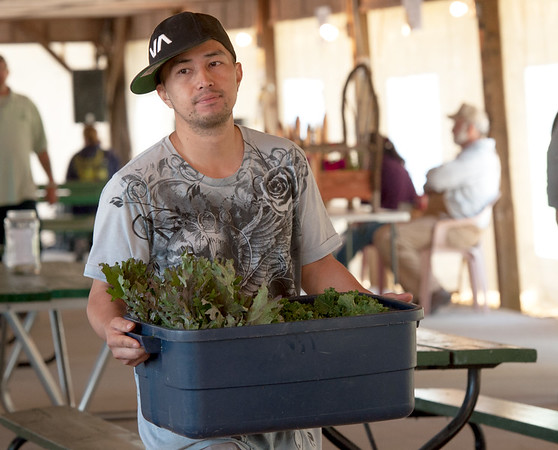 Gee Vang carries a tub of produce from his family's Vang Gardens booth on Thursday afternoon at the Webb City Farmers Market. The market is open of Tuesdays, Thursdays and Saturdays.<br /> Globe | Laurie Sisk