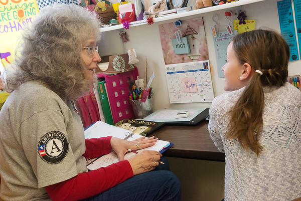 Globe/Roger Nomer<br /> Janel Riley helps Marley Jackson, first grade, with her reading skills on Monday at Purdy Elementary.