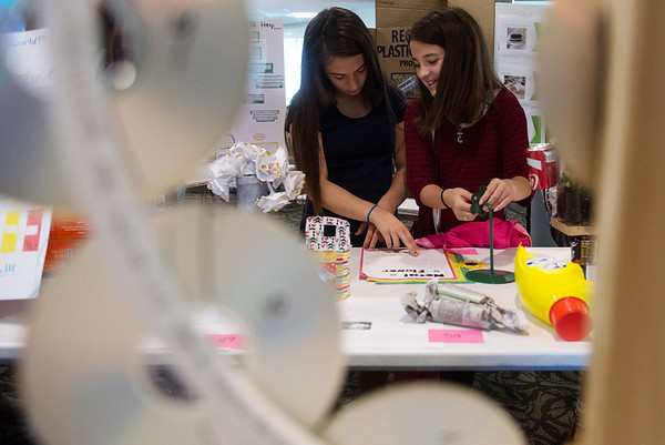 Globe/Roger Nomer<br /> Kourtney Vaughan, left, and Skyler Bowman, seventh graders at Carthage Junior High, look at the recycled crafts, including a clock made from recycled CDs in the foreground, on Tuesday at Missouri Southern.