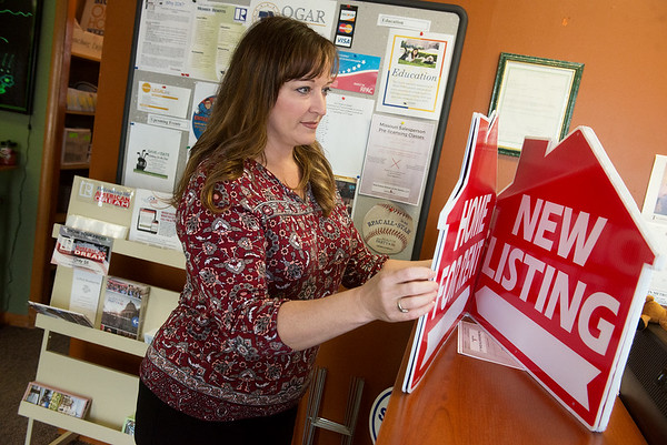 Globe/Roger Nomer<br /> Kim Cox, CEO, sorts through for sale signs at Ozarks Gateway Association of Realtors on Thursday.