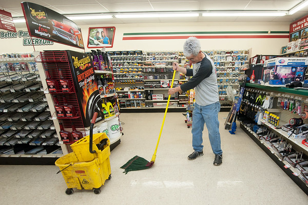 O'Reilly Auto Parts Manager Ken Henry mops his store during cleanup efforts on Sunday in downtown Seneca.<br /> Globe | Laurie Sisk