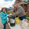 Pastor Larry Convirs, of Wyandotte's Set Free Ministries, serves a hot dog to Tamra Johnson, 17 in downtown Seneca on Sunday. Members of the church were on hand to help feed those displaced by weekend flooding.<br /> Globe | Laurie Sisk