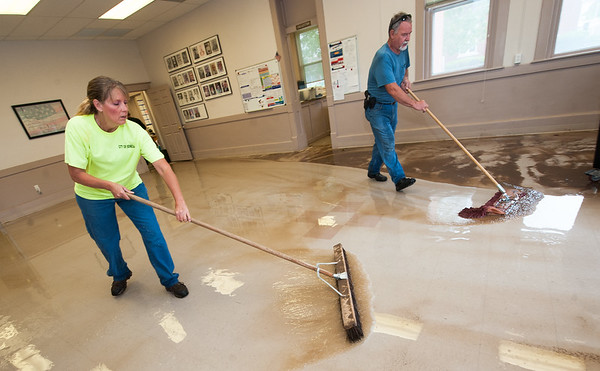 From the left: Melissa Morris and Gary Lankford, of the City of Seneca Public Works, mop up muddy water on Sunday inside City Hall after heavy flooding this weekend.<br /> Globe | Laurie Sisk