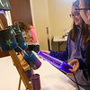 Globe/Roger Nomer<br /> Jordan Baker, left, uses a blacklight to illuminated her recycled cans for Sami Hope, sixth graders at Neosho Middle School, on Tuesday at Missouri Southern.