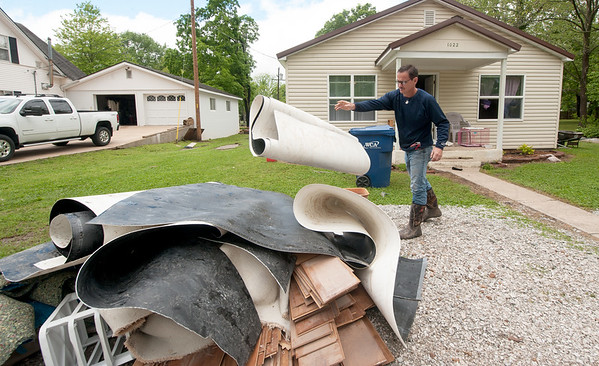 Seneca resident Claude Merriman pitches damaged flooring from his Hamilton Street home on Sunday as cleanup from heavy flooding continues.<br /> Globe | Laurie Sisk