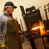 Globe/Roger Nomer<br /> Paul Brown puts a knife in his forge while working on Friday at his studio in Carthage.