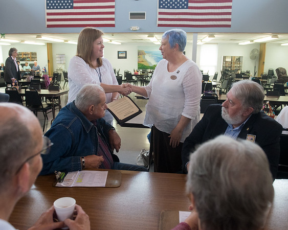 Globe/Roger Nomer<br /> Shelly Goerz, RSVP coordinator, gives a proclaimation to Wendy Wagaman, manager of the Joplin Senior Center, recognizing the center's Meals on Wheels program on Tuesday at the center. Also pictured are Bob Guarino, RSVP volunteer, and Joplin Councilman Gary Shaw.