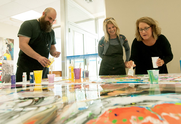 "From the left: Crowder College art instructor Josh Knott, Director of Instructional Advancement Cindy Branscum and Crowder Foundation Adminstrative Assistant Lori Barnes add more color to an abstract acrylic piece during Fine Arts Week on Wednesday at Crowder. Other activities at the college this week include graphic design presentations, a high school theatre workshop and the Johnny Cash musical ""Ring of Fire.""<br /> Globe 