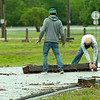 From the left: Neosho residents James Marchisio and Jaymes Wilkins on Saturday remove a large railroad tie that washed onto La-Z-Boy Drive near Morris Park in Neosho after heavy rains Friday night and Saturday caused massive flooding in the area.<br /> Globe | Laurie Sisk