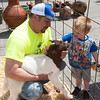 Mike McCann, of Grace Farms, holds a young male goat for three-year-old Reid McCallister during the Junkin' Joplin Downtown Market on Saturday near 6th and Main streets.<br /> Globe | Laurie Sisk