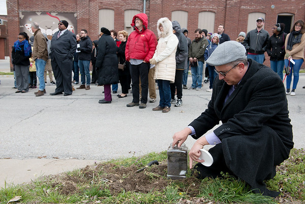 Travis Hurley, director of advancement at Watered Gardens, collect soil from the site of the lynching of Thomas Gilyard at Second and Wall on Sunday afternoon. <br /> Globe   Roger Nomer