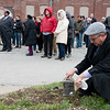 Travis Hurley, director of advancement at Watered Gardens, collect soil from the site of the lynching of Thomas Gilyard at Second and Wall on Sunday afternoon. <br /> Globe | Roger Nomer
