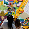 Visitors watch Kris Kanaly, from Oklahoma City, Okla., work on his mural in downtown Miami on Saturday during Mural Fest 66.<br /> Globe | Roger Nomer