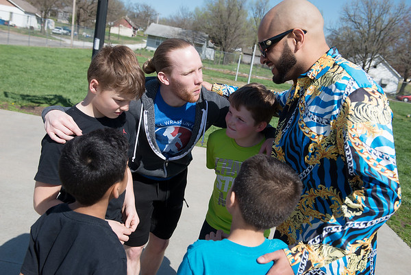NWL wrestlers Jax Royal, left, and Rasheed Ali huddle up with their team before playing basketball at the Joplin Boys and Girls Club on Thursday.<br /> Globe   Roger Nomer