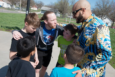 NWL wrestlers Jax Royal, left, and Rasheed Ali huddle up with their team before playing basketball at the Joplin Boys and Girls Club on Thursday. Globe | Roger Nomer