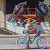 Aubrie Foran, 7, stops to watch Ana Maria Ortiz, who goes by the artist name Anamarietta, paint a mural at the Miami Public Library on Saturday. Ortiz is orginally from Puerto Rico, where she studied Animal Sciences. Her murals feature creatures of her own creation, like these waterfowls.<br /> Globe | Roger Nomer