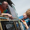 """Eli Cole, 2, and his grandmother Kathie, Joplin, have a free Kona Ice served by Ty Levens during Tuesday's """"No Taxation Without Relaxation"""" event. Kona Ice provided free shaved ice treats on Tax Day in the parking lot of the Habitat for Humanity Restore.<br /> Globe 