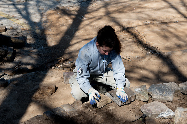 AmeriCorps National Civilian Community Corps member Paige O'Neil, Canandaigua, N.Y., work on a landscaping project at the Bluejacket Building in Seneca on Monday.<br /> Globe | Roger Nomer
