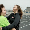 Erica Michaels, 14, right, gives her East Newton teammate Morgan McCracken, 17, a hug as McCracken crosses the finish line during Wednesday's Special Olympics Missouri regional track and field meet at Haffner Stadium in Carthage.<br /> Globe | Roger Nomer