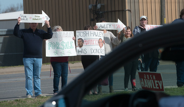 A group of protesters hold signs outside Missouri Attorney General Josh Hawley speech at Able Manufacturing on Friday afternoon.<br /> Globe | Roger Nomer