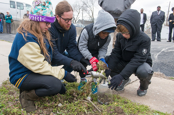 (from left) Paige, 12, Shane, Robert, 5, and Maddox, 10, Wood, of Joplin, collect soil from the site of the lynching of Thomas Gilyard at Second and Wall on Sunday afternoon.<br /> Globe | Roger Nomer