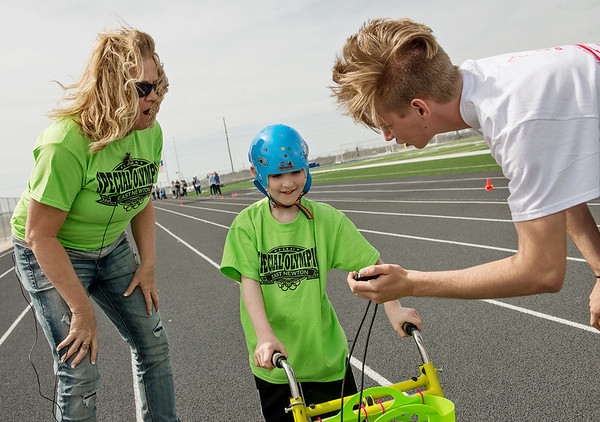 Clay Stout, Carthage High senior, shows Thomas Perkins, 8, East Newton, and Kristi Harvill Perkins' finishing time during Wednesday's Special Olympics Missouri regional track and field meet at Haffner Stadium in Carthage.<br /> Globe | Roger Nomer