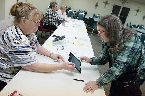 Helen Bishop, left, helps Beth Routledge sign in to vote at the Joplin Association for the Blind on Tuesday.<br /> Globe | Roger Nomer