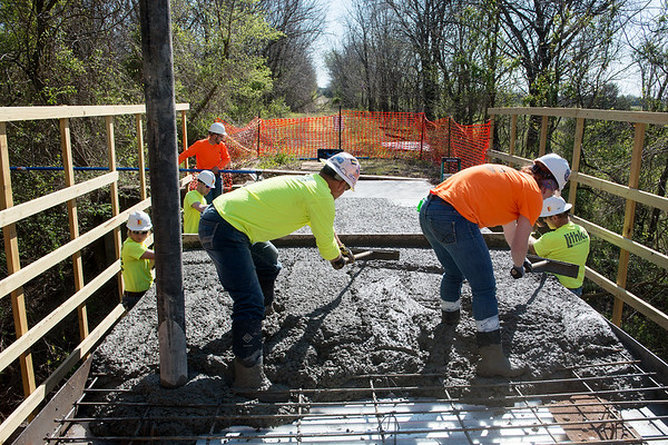 Pittsburg State University students and staff pour concrete at the Ruby Jack Trail bridge on Tuesday.<br /> Globe   Roger Nomer