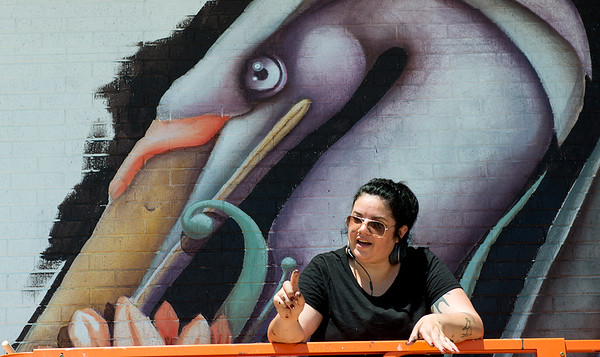 Ana Maria Ortiz, who goes by the artist name Anamarietta, talks with visitors about her mural on the Miami Public Library during Mural Fest 66 on Saturday afternoon. Ortiz is orginally from Puerto Rico, where she studied Animal Sciences. Her murals feature creatures of her own creation, like these waterfowls.<br /> Globe | Roger Nomer
