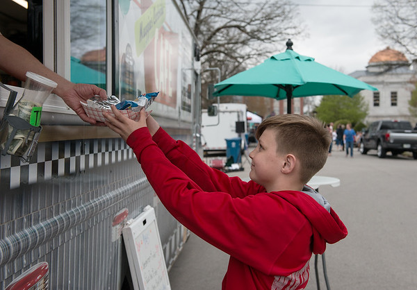 Morgan Vaughn, 12, Seneca, gets an order from Maggie's Curbside Cafe during Food Truck Friday in Carthage's Central Park.<br /> Globe   Roger Nomer