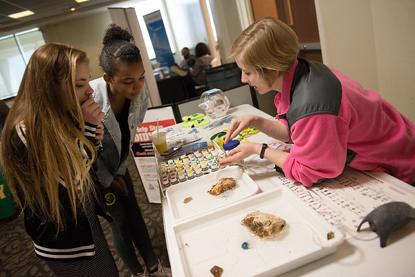 Lily Kennedy, with the Missouri Stream team, shows macroinvertebrates to Emma Trewyn, left, and Olivia Jackson, eighth graders at Carl Junction Middle School, during an early Earth Day event at Missouri Southern on Wednesday.