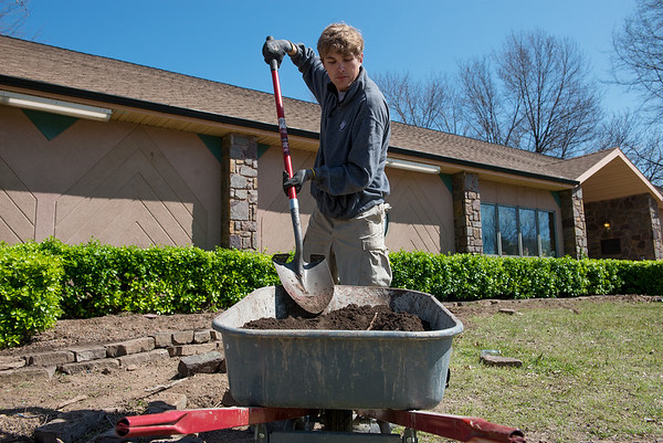 AmeriCorps National Civilian Community Corps member Paul Goehring, Seattle, Wash., works on a landscaping project at the Bluejacket Building in Seneca on Monday.<br /> Globe   Roger Nomer