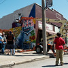 Visitors watch students with the NEO A&M College Art Program create a mural in downtown Miami for Mural Fest 66 on Saturday.<br /> Globe | Roger Nomer