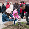 Howie Nunnelly, right, helps Zarah Vylonis and her goddaughter Ella Howerton, 2, collect soil from the site of the lynching of Thomas Gilyard at Second and Wall on Sunday afternoon.<br /> Globe | Roger Nomer