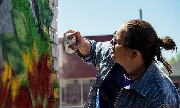 Colleen Garrett, a NEO College senior from Afton, paints a mural in downtown Miami on Saturday for Mural Fest 66.<br /> Globe | Roger Nomer