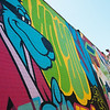 Kris Kanaly works on his mural in downtown Miami as a completed mural by Jake Beeson is in the foreground on Saturday during Mural Fest 66.<br /> Globe | Roger Nomer