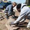 AmeriCorps National Civilian Community Corps members Paul Goehring, Seattle, Wash., and Anisha Adderly, West Palm Beach, Fla., work on a landscaping project at the Bluejacket Building in Seneca on Monday.<br /> Globe | Roger Nomer