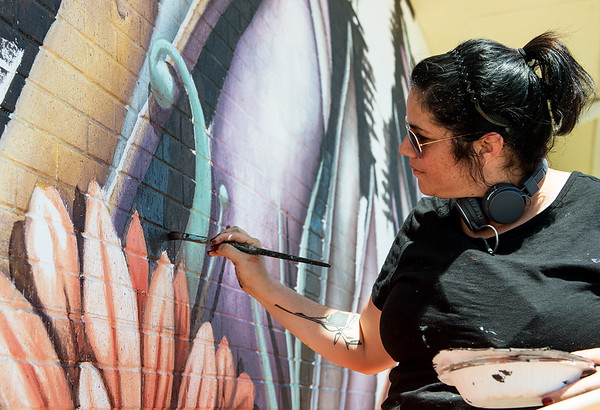 Ana Maria Ortiz, who goes by the artist name Anamarietta, paints a mural on the Miami Public Library during Mural Fest 66 on Saturday afternoon. Ortiz is orginally from Puerto Rico, where she studied Animal Sciences. Her murals feature creatures of her own creation, like these waterfowls.<br /> Globe | Roger Nomer