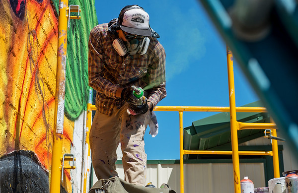 Yatika Fields tests a spray can while painting his mural in downtown Miami on Saturday during Mural Fest 66. <br /> Globe   Roger Nomer