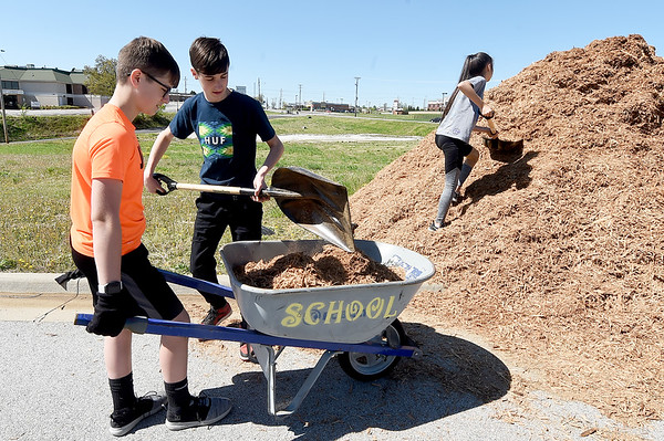 From the left: Carl Junction LEO volunteers Alex Brownstein, 15, Jackson Hinderliter and Madeleine Garoutte, 13, transport fresh mulch for landscaping at Irving Elementary on Saturday. About 13 kids from LEO joined two of their advisers and 20 volunteers from the M6 District of Lions Club planting trees, spreading mulch and building a pergola. LEO (Leadership, Experience and Opportunity) is an extension of the Lions Club International.<br /> Globe | Laurie Sisk